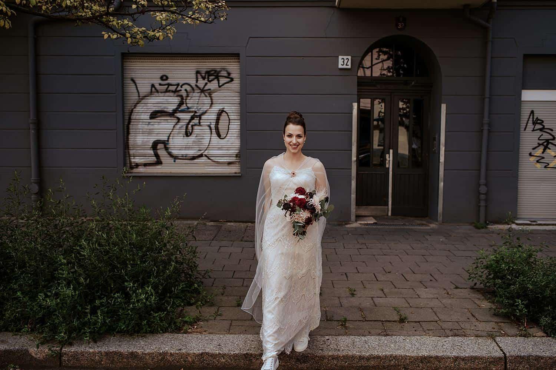 hochzeitskleid mit umhang und Burgunder Blumenstrauß,